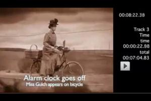 "The clocks of ""Time"" all go off to signify Miss Gultch's arrival on bicycle..."